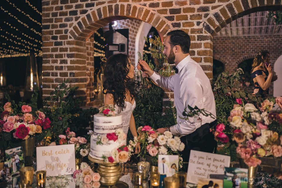 groom feeds bride wedding cake at flora farms wedding photograph