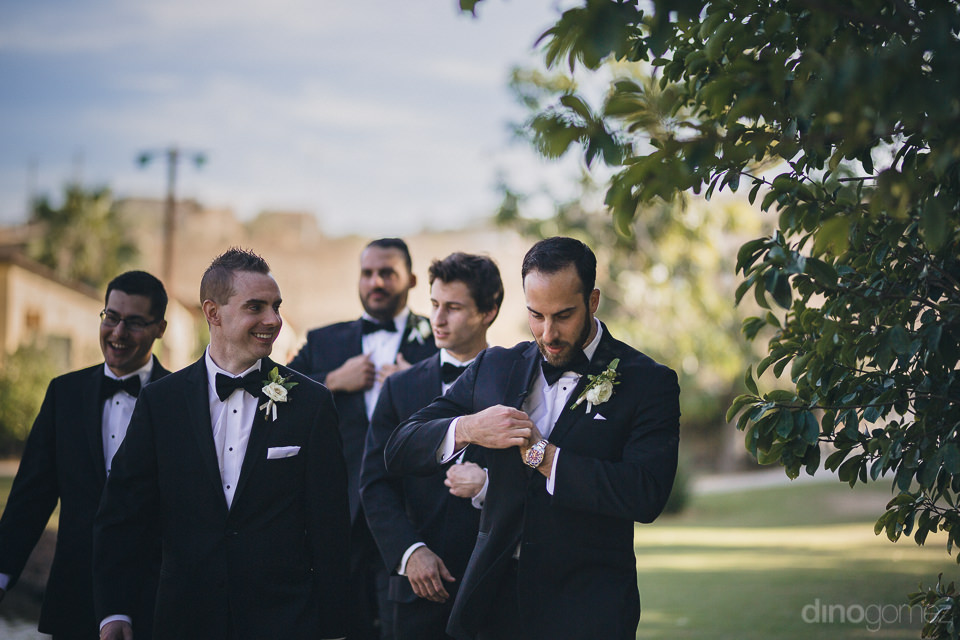 groom and four groomsmen in matching suits arrive to outdoor far