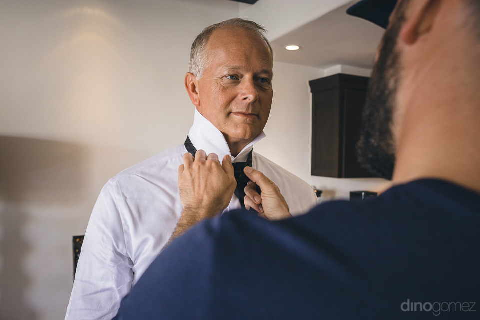 groom helps put on tie as they prepare for the wedding photo by