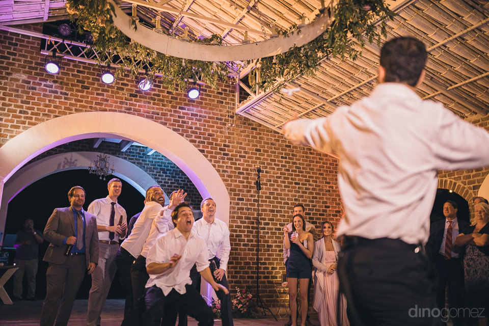 groom throws bridal garter to male wedding guests waiting to cat