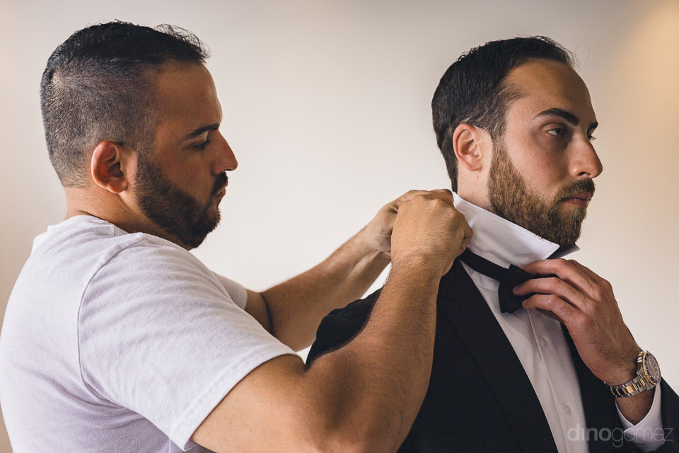 groomsmen helps groom to put on his bow-tie as they prepare for
