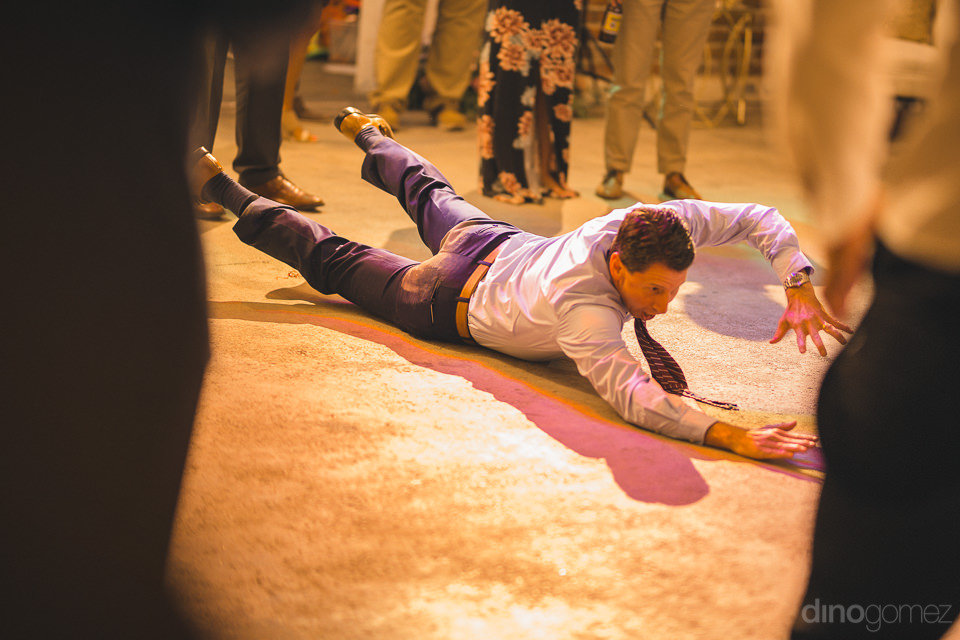 wedding guest having fun breakdancing at wedding reception