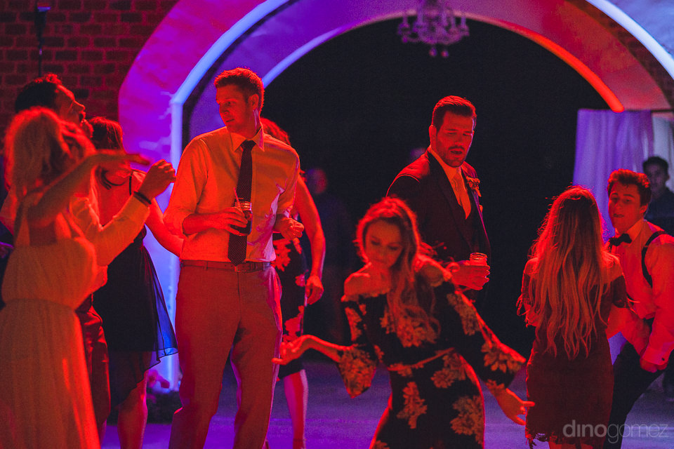 wedding guests dance under red light in unique interesting weddi