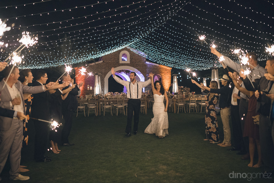 wedding guests hold up sparklers as the bride and groom pass by