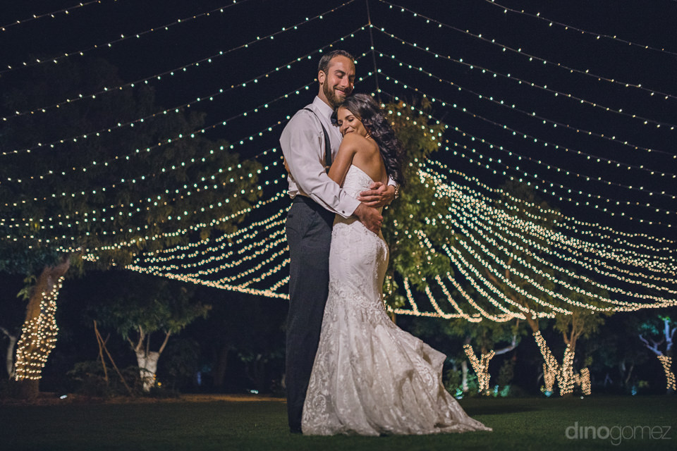 newlyweds under bright tent lights at luxury wedding photographe