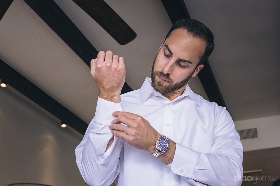 handsome groom wears watch and cufflinks for his luxurious weddi