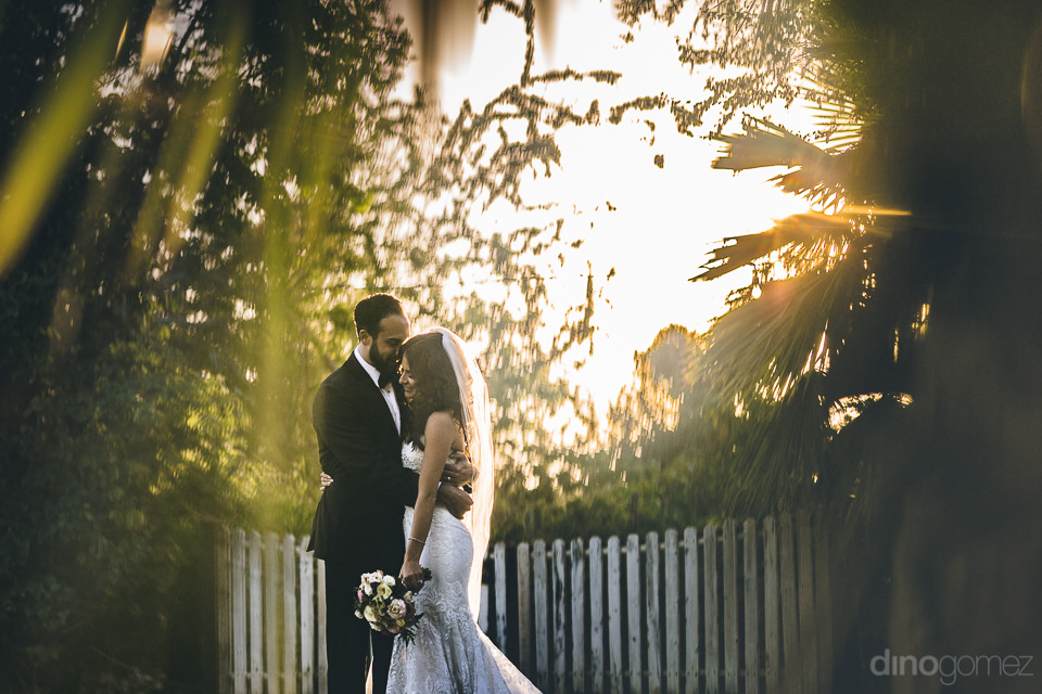newlyweds embrace in a secluded part of the garden on their wedd