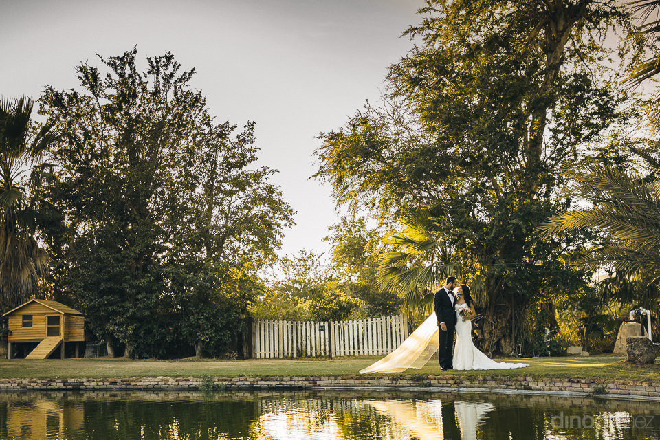 newlyweds pose next to pond in green natural outdoor wedding pho