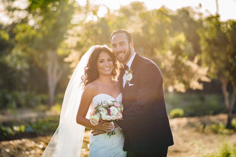 newlyweds stand in sunny orchard in wedding photo by dino gomez