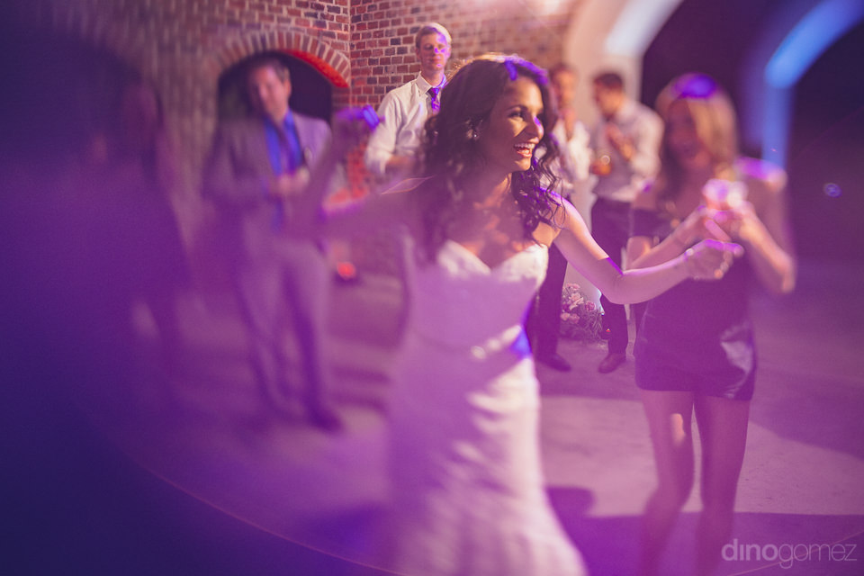 fun action photo of bride dancing with wedding guests at flora f