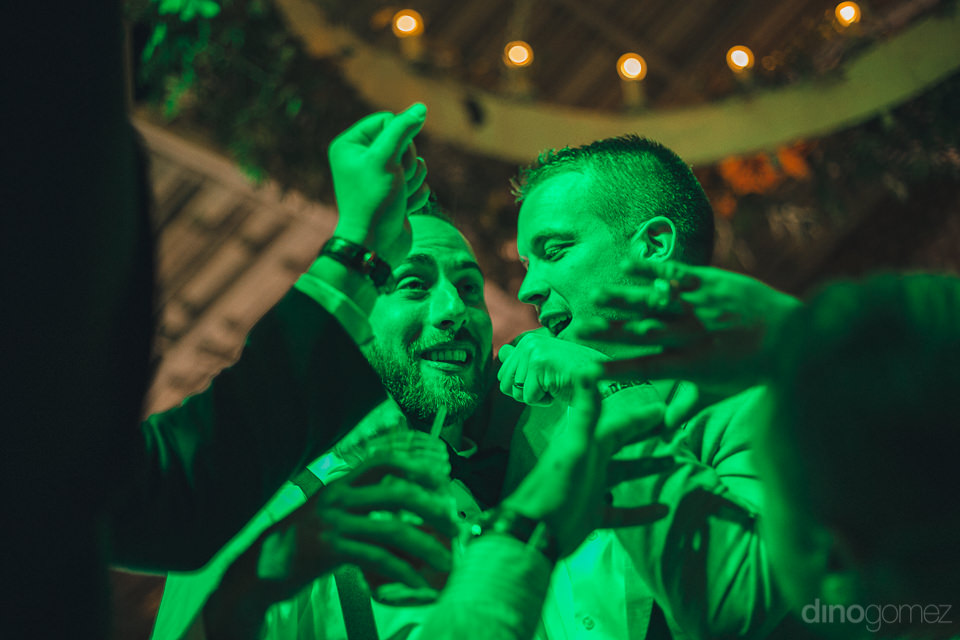 groom and groomsmen illuminated in green light as they party at