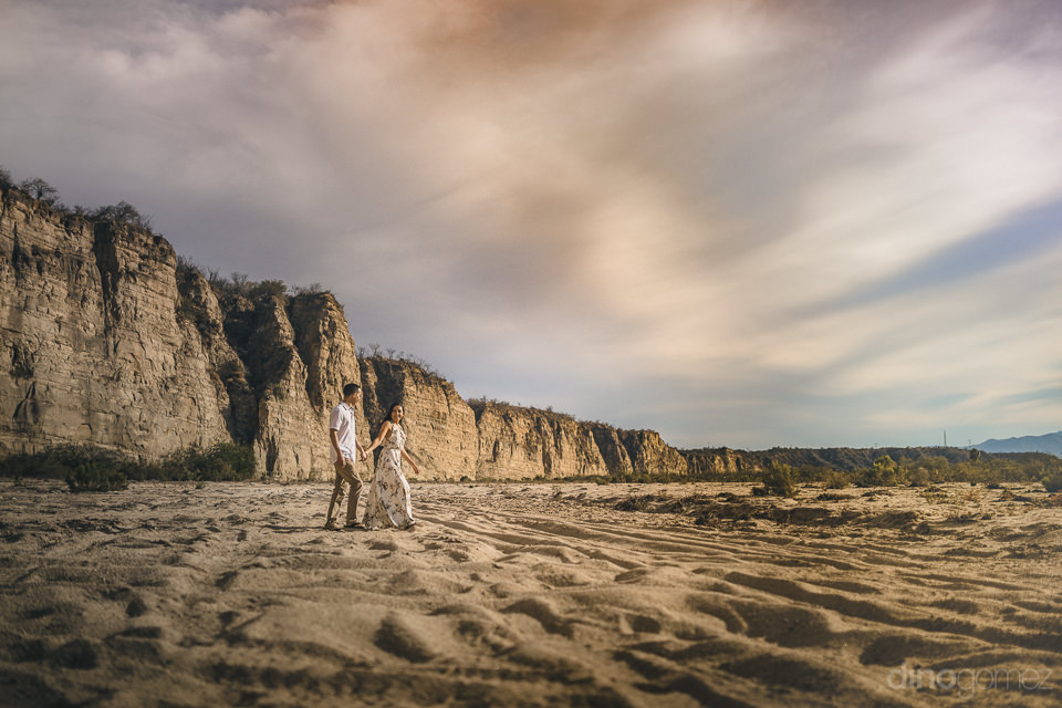 young newlyweds walk through sand next to rock cliff face in baj