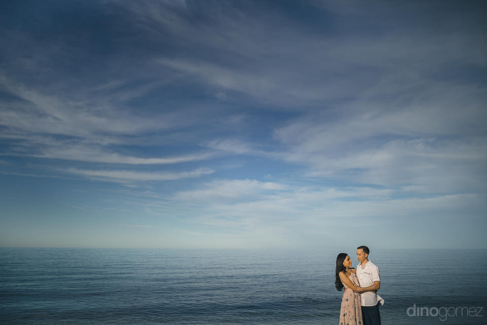 calm blue ocean water and slightly cloudy blue sky with newlywed