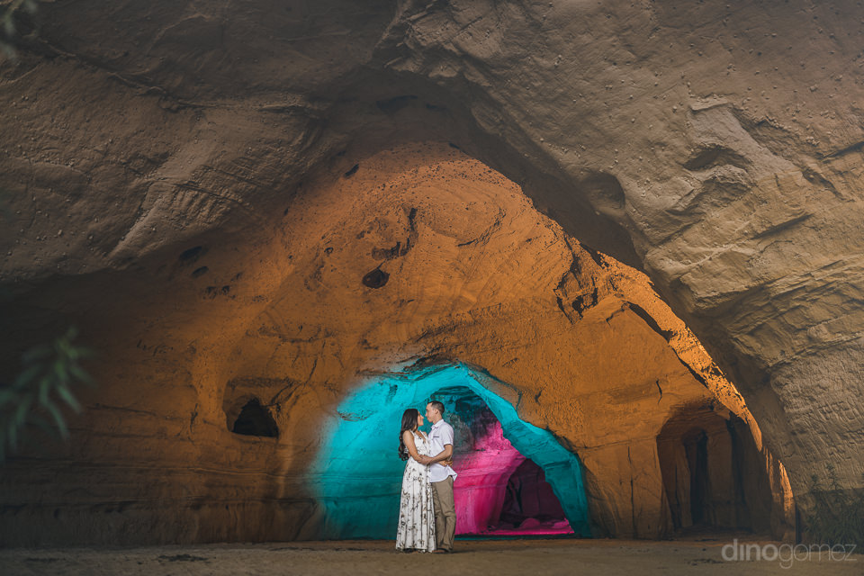 local photographer dino gomez inside colorful cave with newlywed