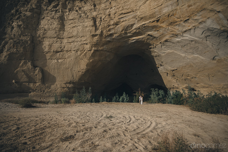 newlyweds stand in front of huge rock face with cave in baja cal