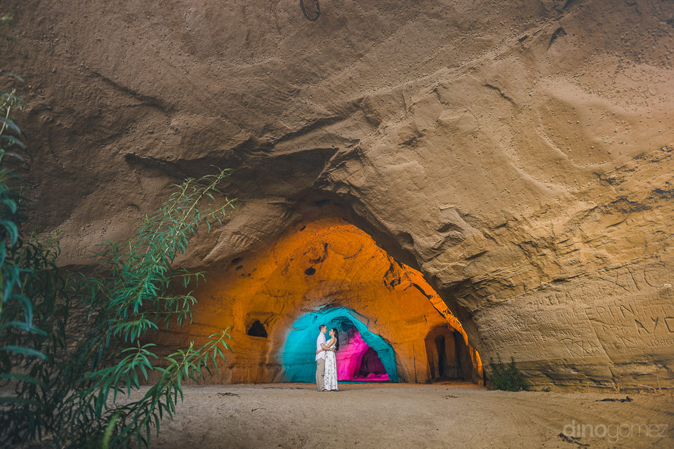 artistic wedding photo of newlyweds standing in rock tunnel cave