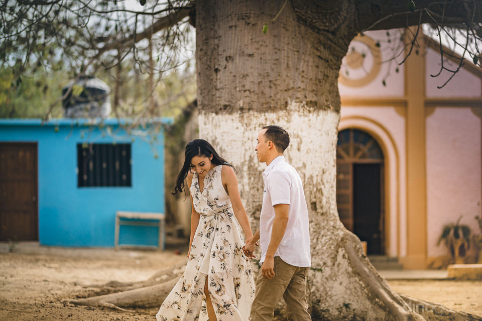 young newlyweds stand in front of big tree in quaint small mexic