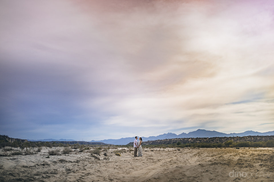 long shot of newlyweds together in vast open desert in mexico