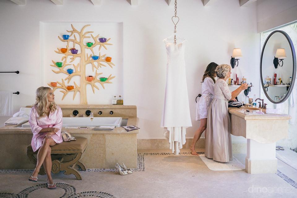 wedding dress hangs in room as bride mom and maid of honor get r