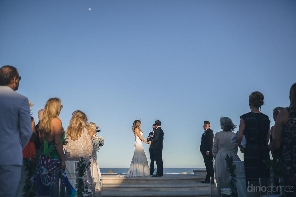 blue sky bride groom at altar wedding photo by dino gomez