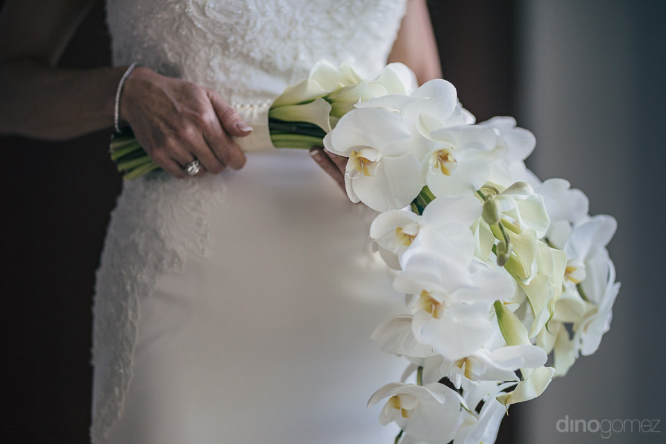 bride in white dress holding bouquet made by cabo floral studio