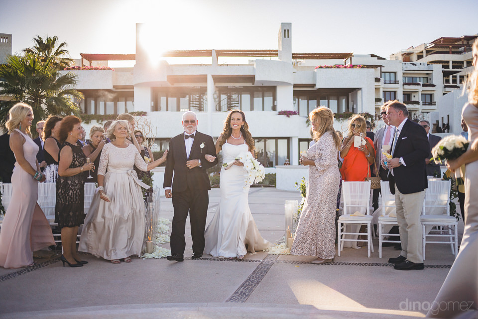 father walks bride down the aisle at outdoor luxury wedding cere