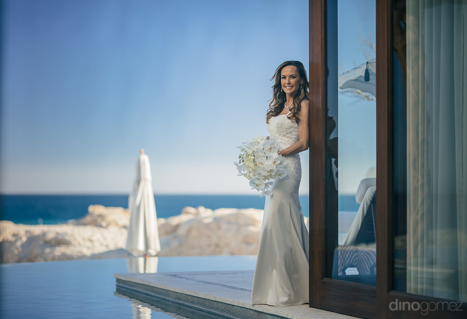 bride holds bouquet and poses for photo by luxury destination we