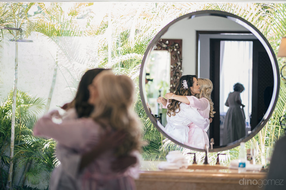 bride and bridesmaid reflection in big round mirror in photo by