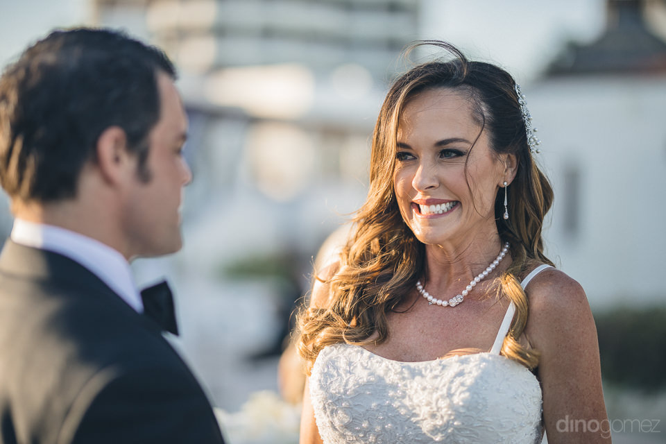 cabo photographer dino gomez photo of bride smiling at groom dur