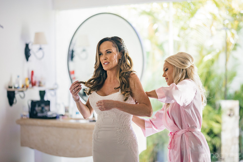 bridesmaid helps bride put on wedding dress on morning of weddin