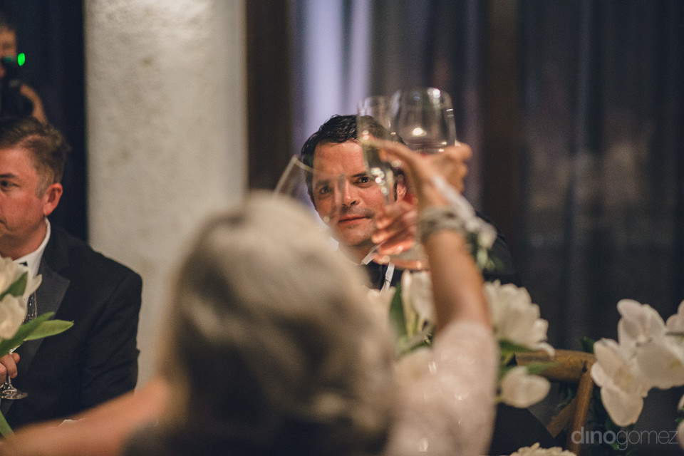 the newlyweds and guests hold up their glasses for a toast at di