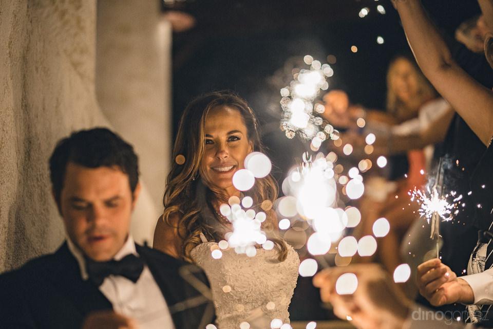 bride and groom walk among sparklers at destination wedding rece