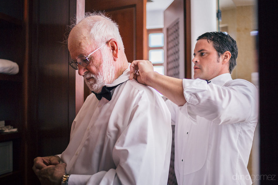 groom puts on his fathers bow-tie on wedding day in cabo