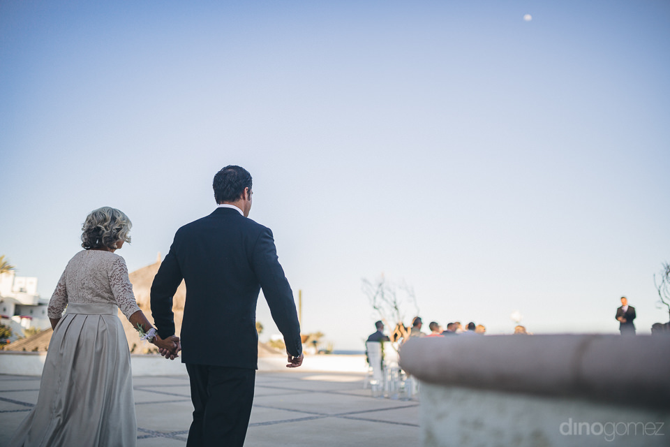 beachside wedding ceremony groom and mother walk to ceremony a l