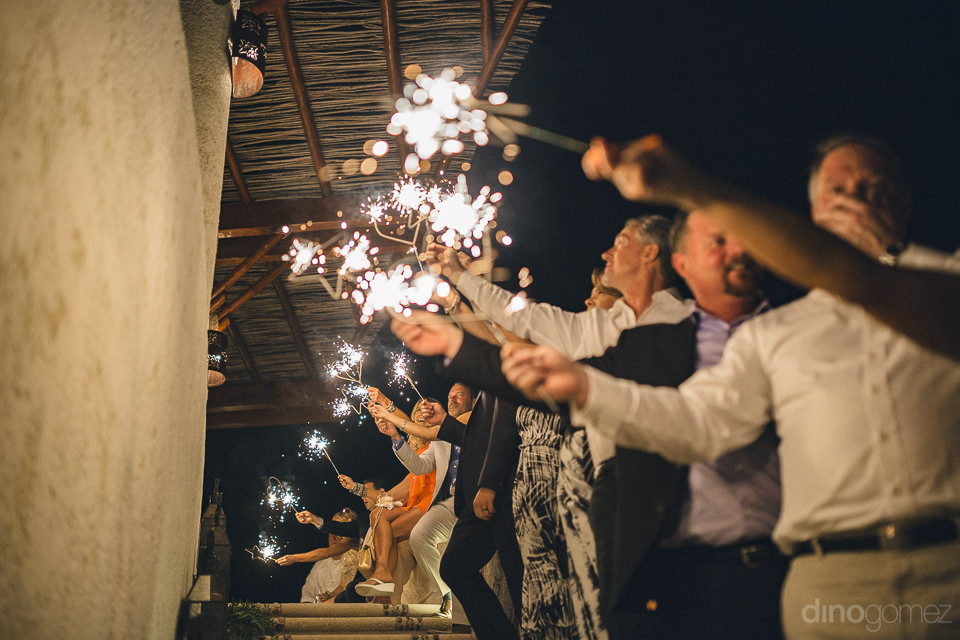 newlyweds arrive to reception and guests hold out sparklers