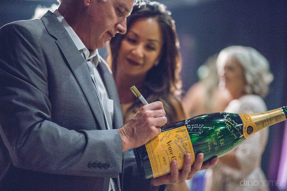 guests sign champagne bottle for newlyweds