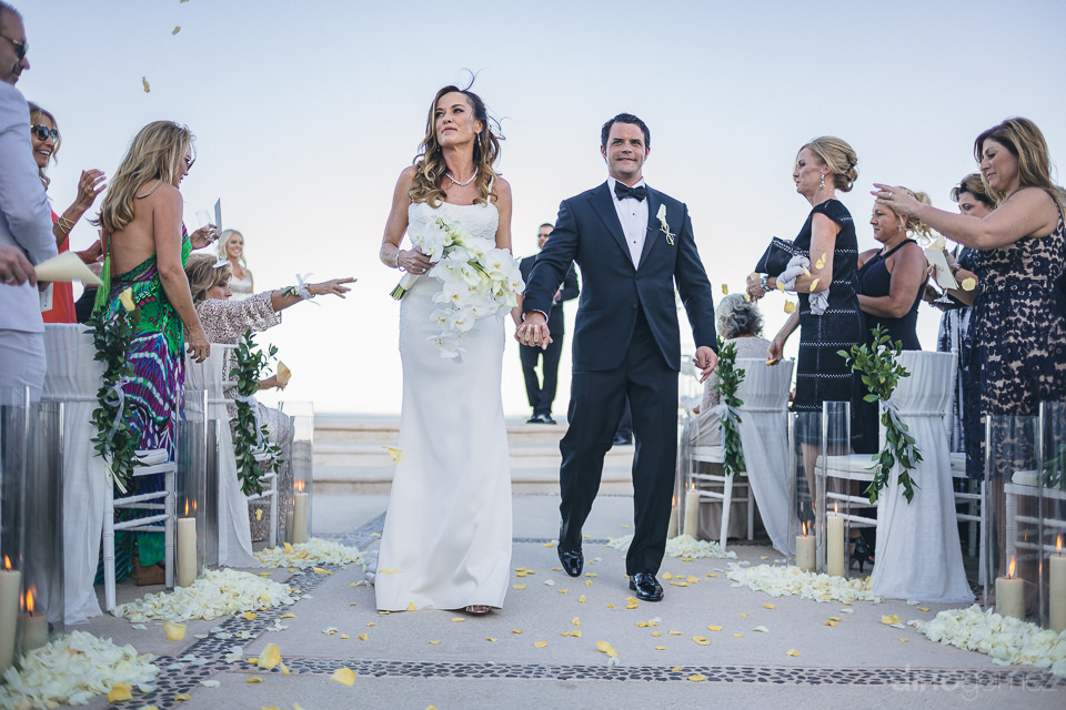 bride and groom walk away as newlyweds hand in hand at los cabos