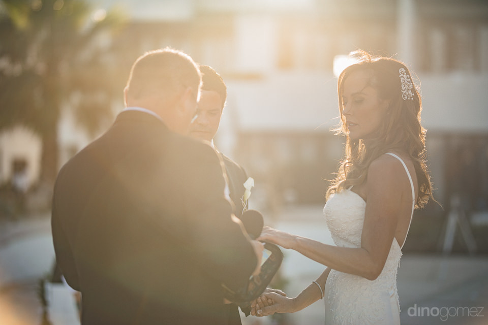 groom puts ring on brides finger at luxury wedding ceremony in l
