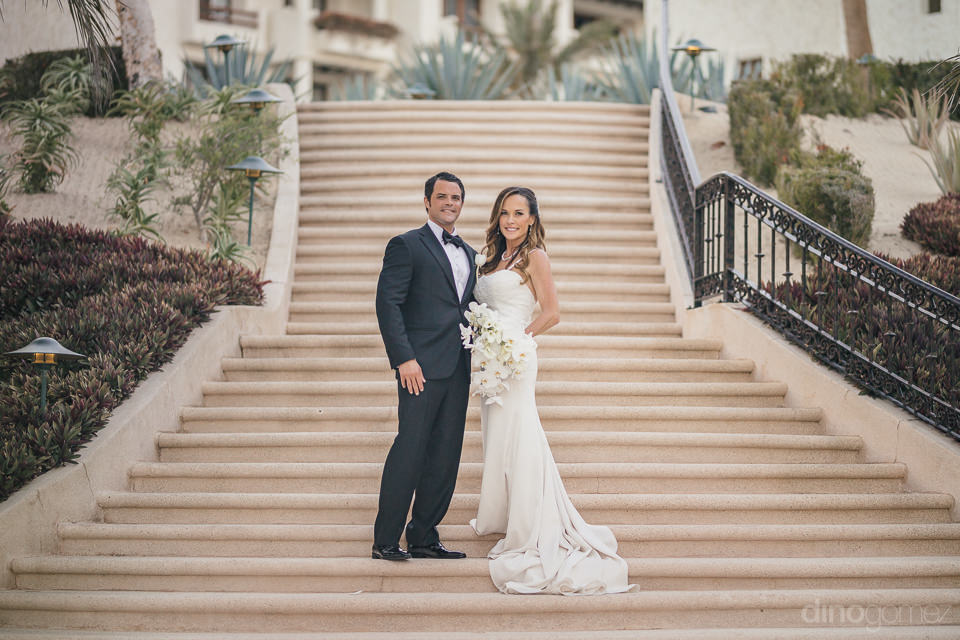 newlyweds stand on long stairway at luxury mexican villa resort