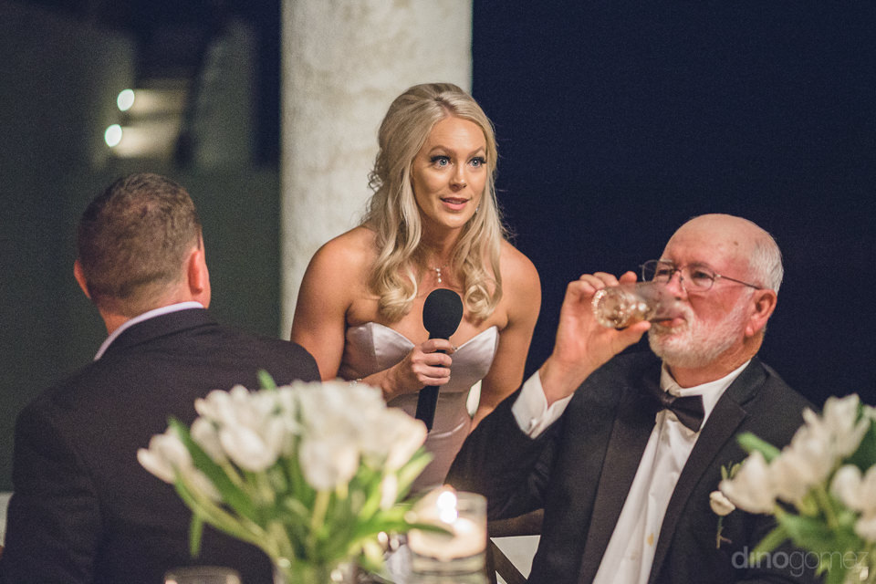 maid of honor holds microphone and speaks during luxury wedding