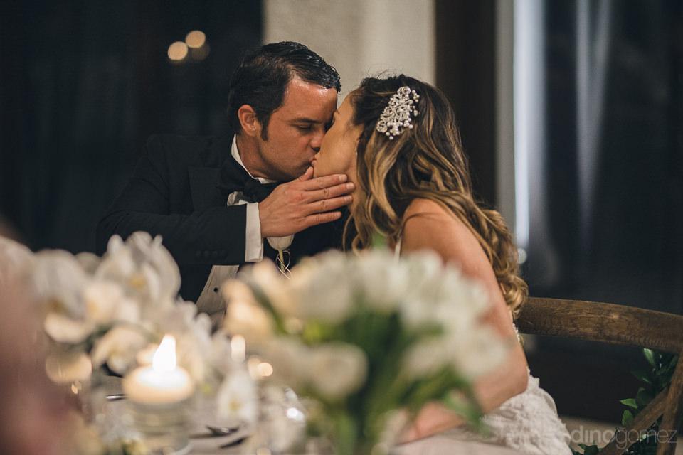 good looking newlyweds kiss at wedding reception