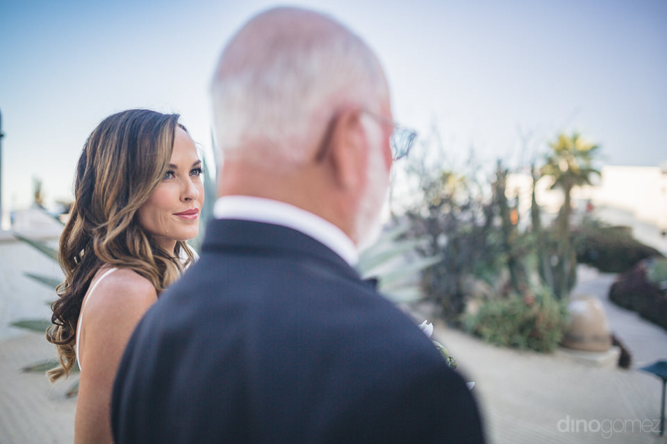 bride walks with father toward wedding ceremony overlooking the