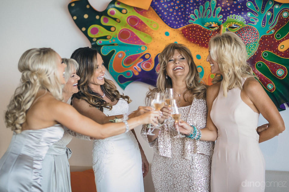 pretty ladies and bride drink champagne before cabo wedding phot