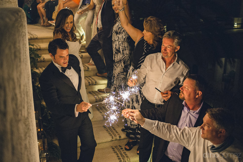 wedding guests hold sparklers as bride and groom pass by