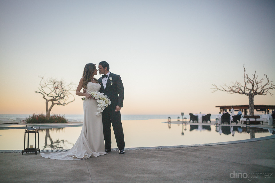 newlyweds stand by pool at sunset in wedding photo by dino gomez