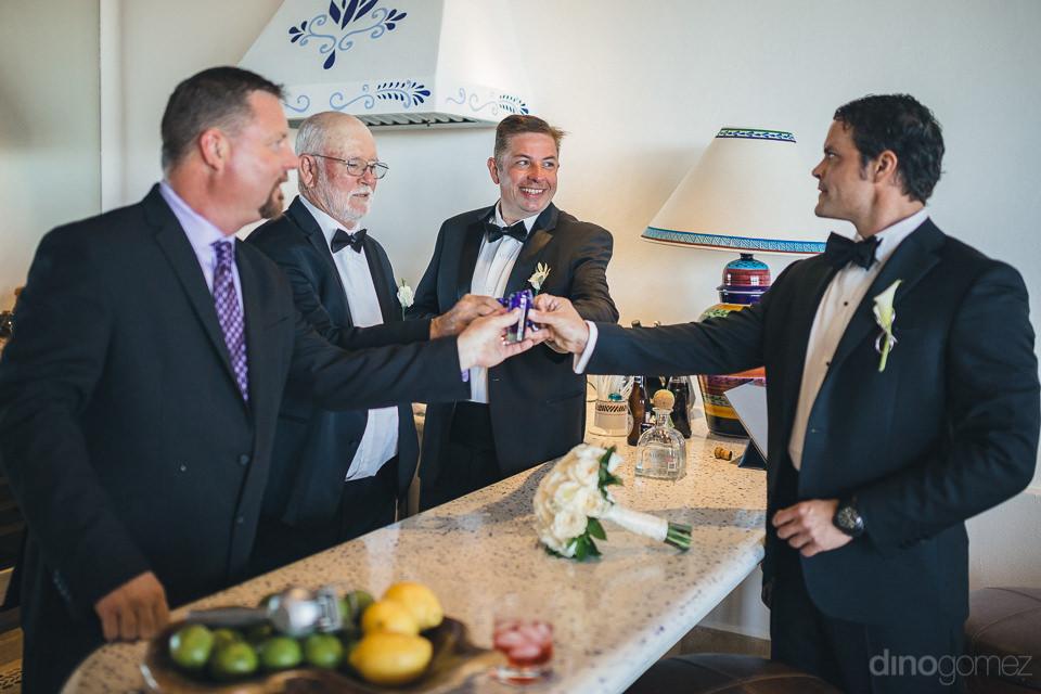 groom and groomsmen drink tequila before luxury destination wedd