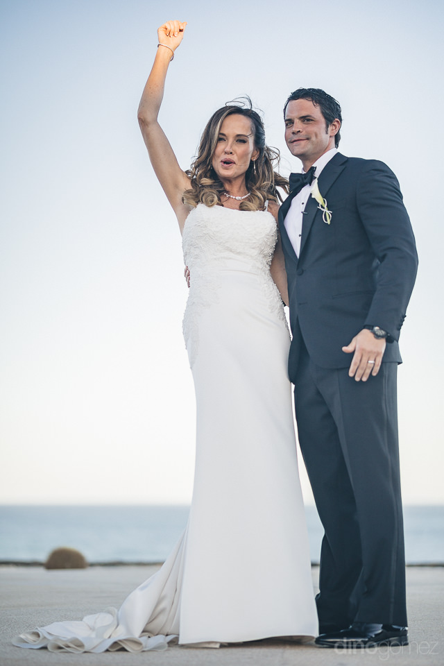 bride and groom celebrate moments after tying the knot in cabo d