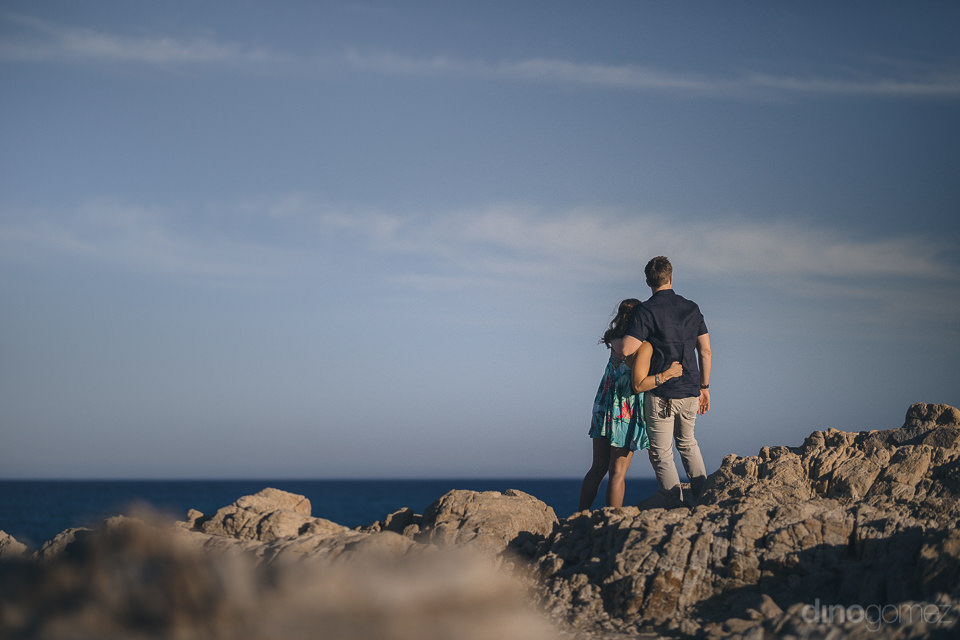 young engaged couple stand atop beach rocks and look out over th