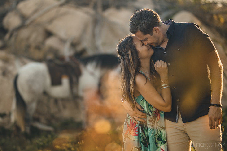 romantic photo of couple standing in front of horse at sunset in