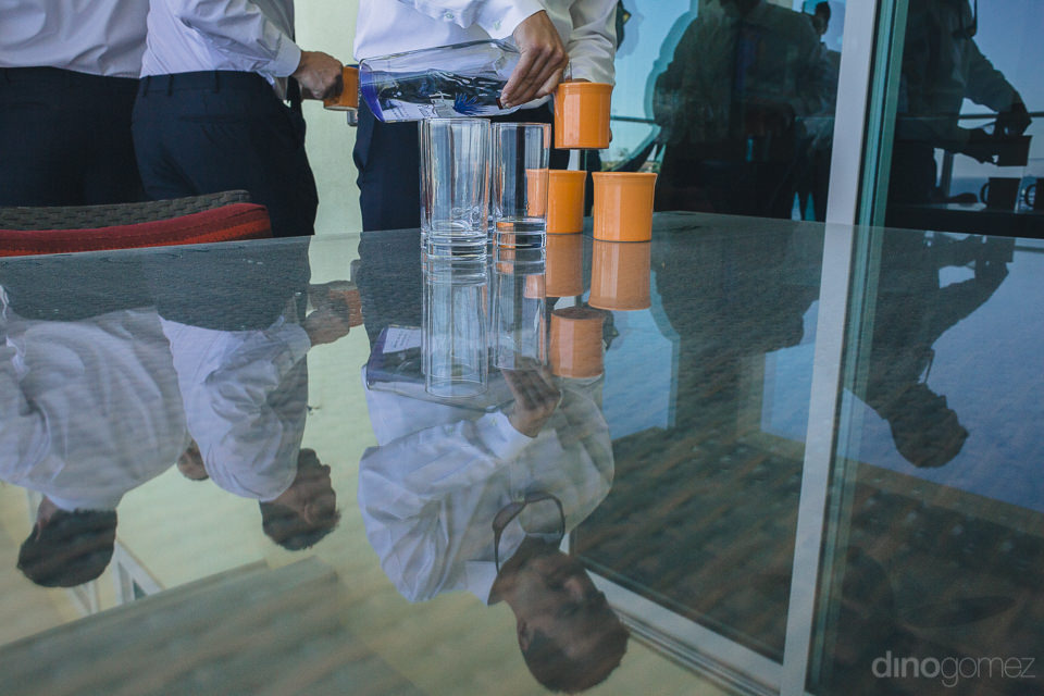 groomsmen drink before wedding reflected in glass table artistic